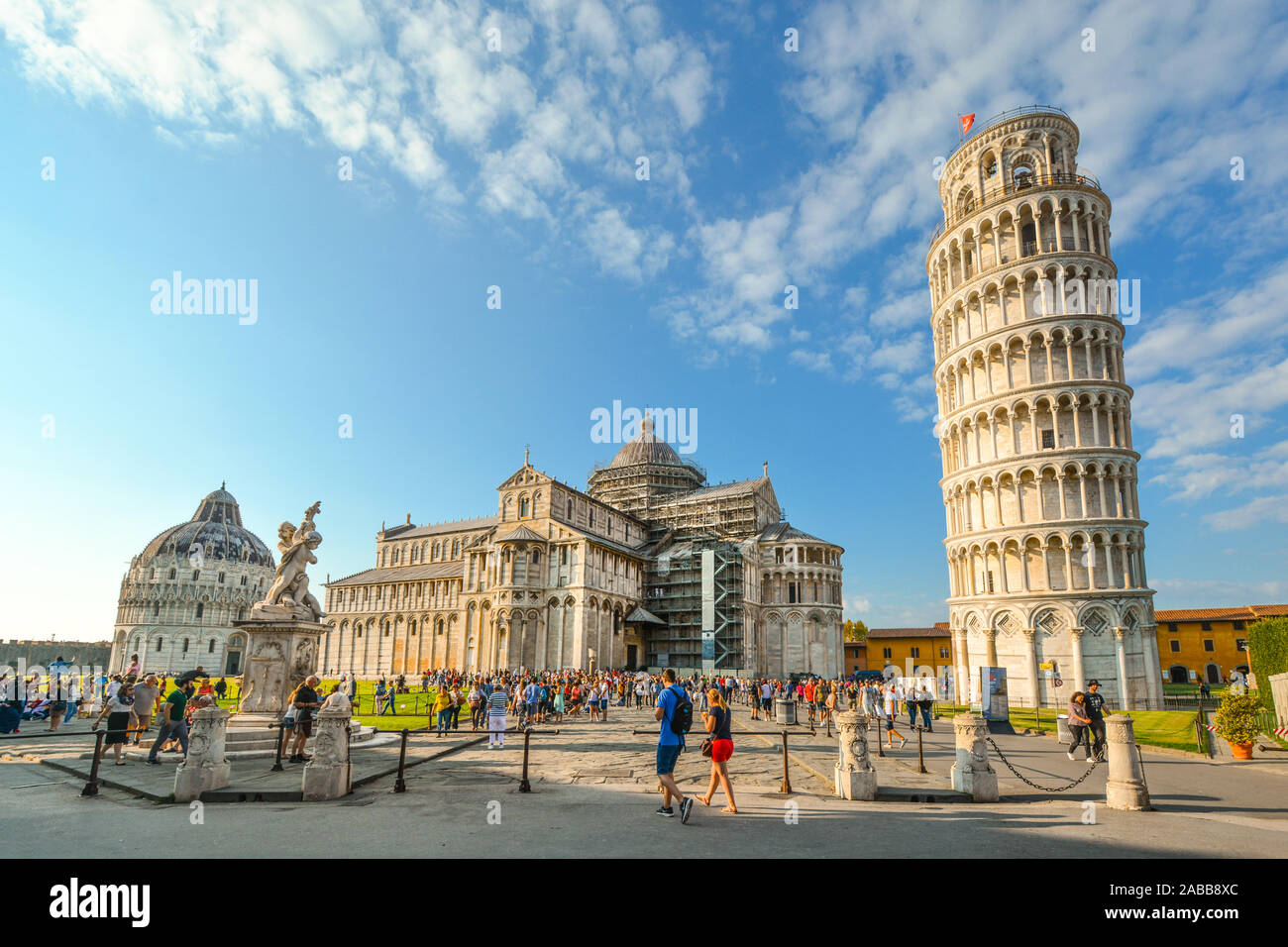 Tourists fill the Field of Miracles and Cathedral square alongside the Leaning Tower, Baptistery and Duomo in the Tuscan city of Pisa, Italy Stock Photo