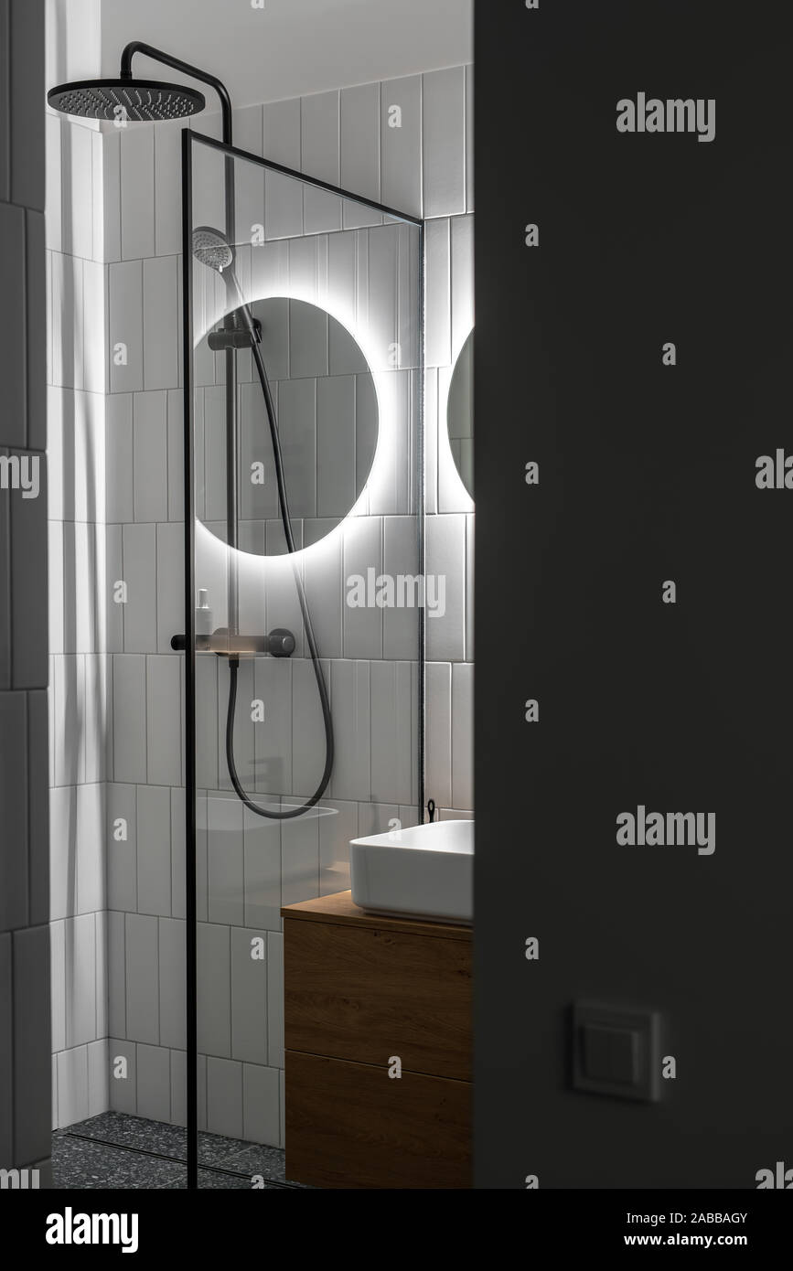 Modern Luminous Bathroom With Tiled White Walls And Textured Dark Gray Floor There Is A Black Shower Glass Partition Round Mirror With Backlight W Stock Photo Alamy