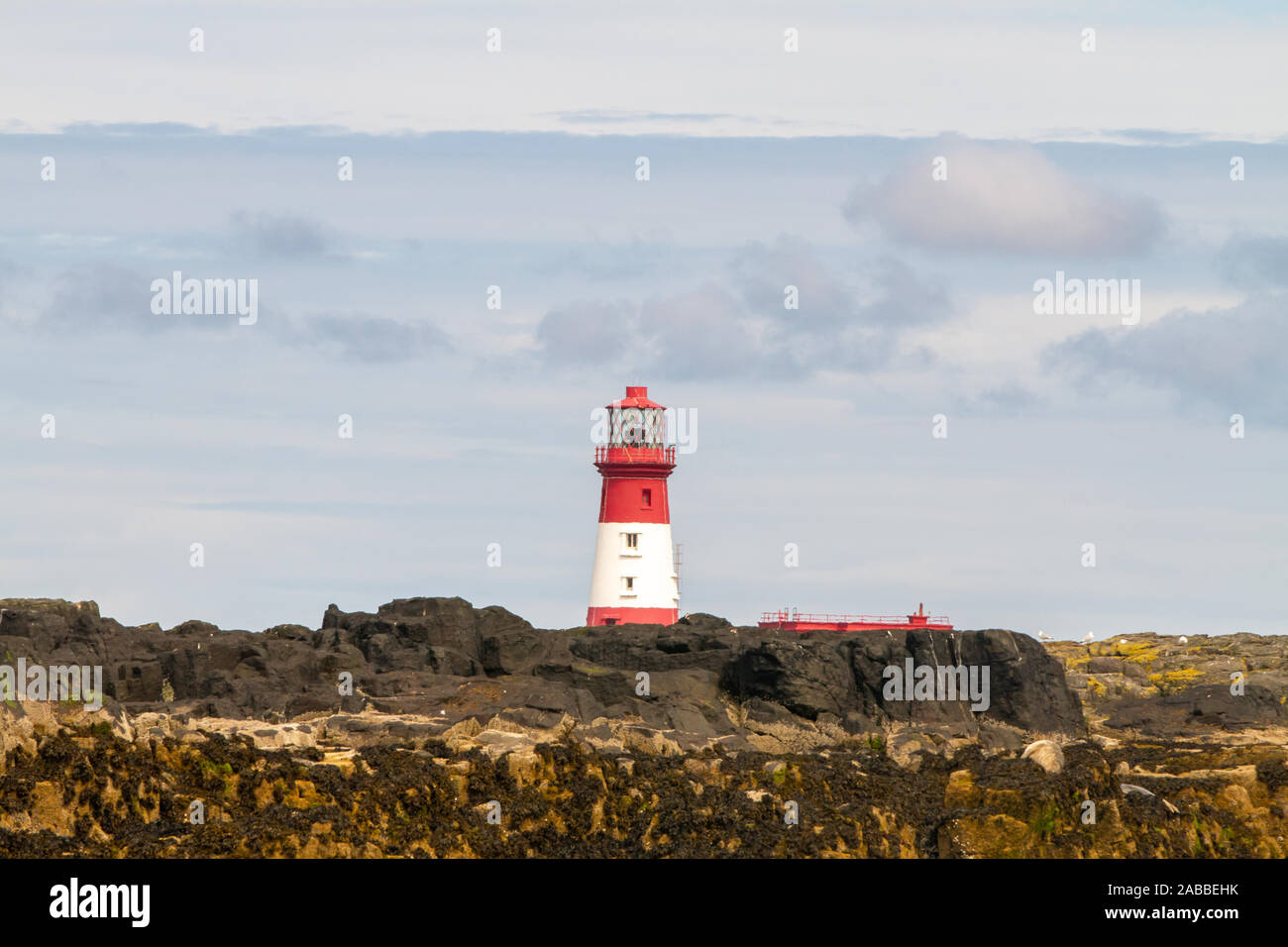 Longstone Lighthouse in white and red, on Longstone Rock in the outer group of the Farne Islands off the Northumberland Coast Stock Photo
