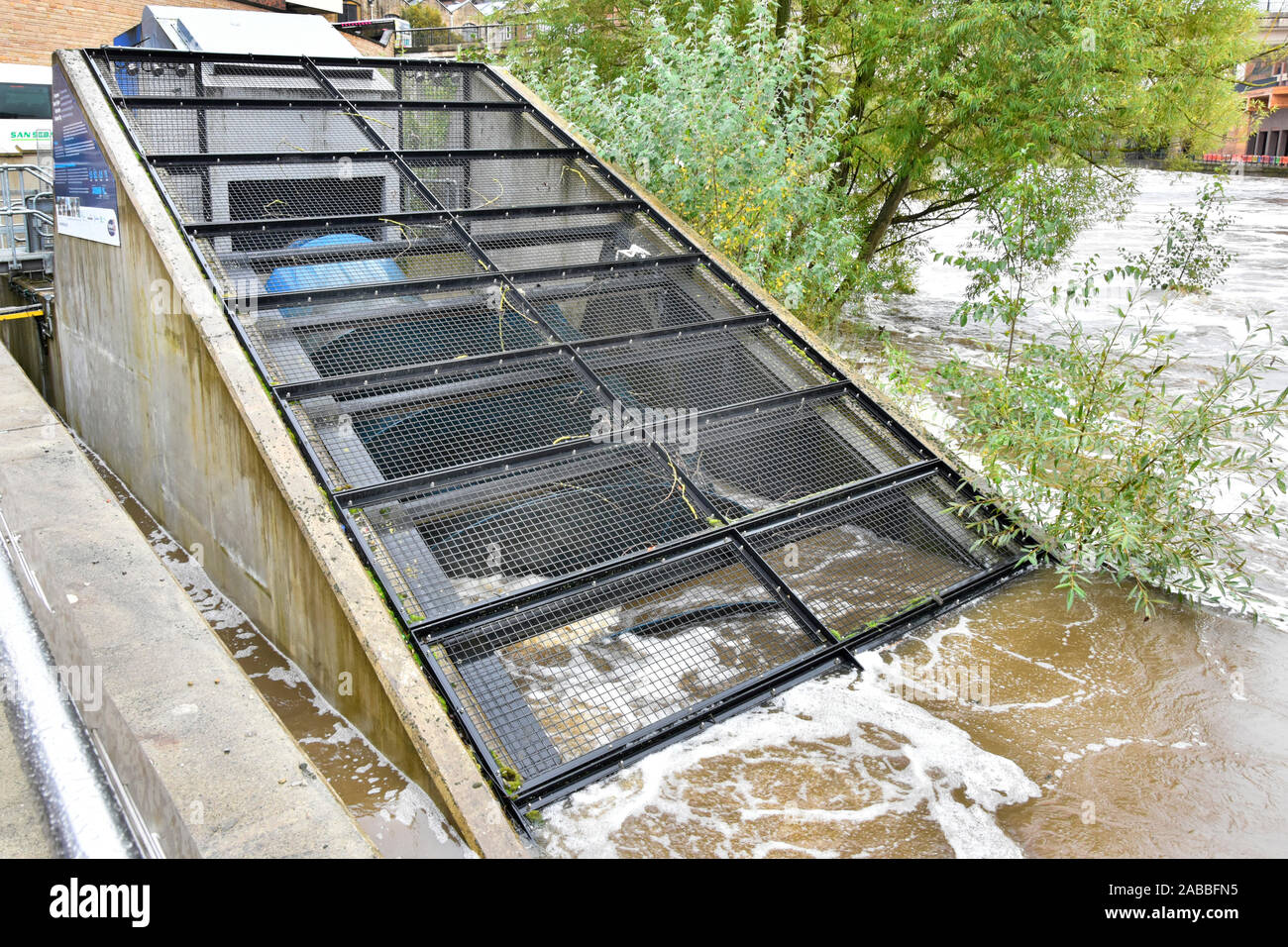 Part of archimedean screw behind security cage being driven by River Wear fast water flow in hydro electricity power generator installation Durham UK Stock Photo