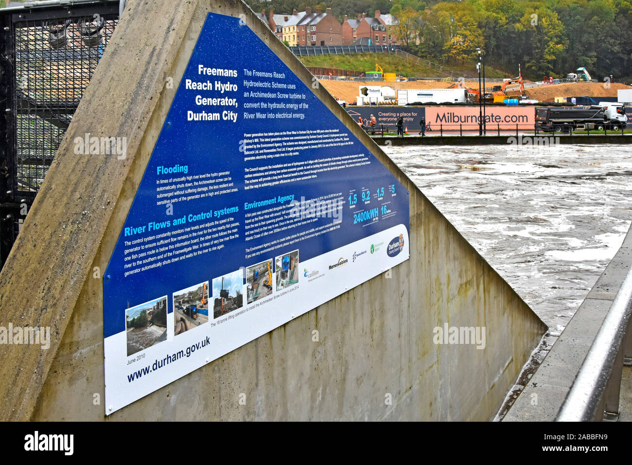 Side wall hydro electricity power generator installation information panel & River Wear fast water flow during potential flood risk Durham England UK Stock Photo