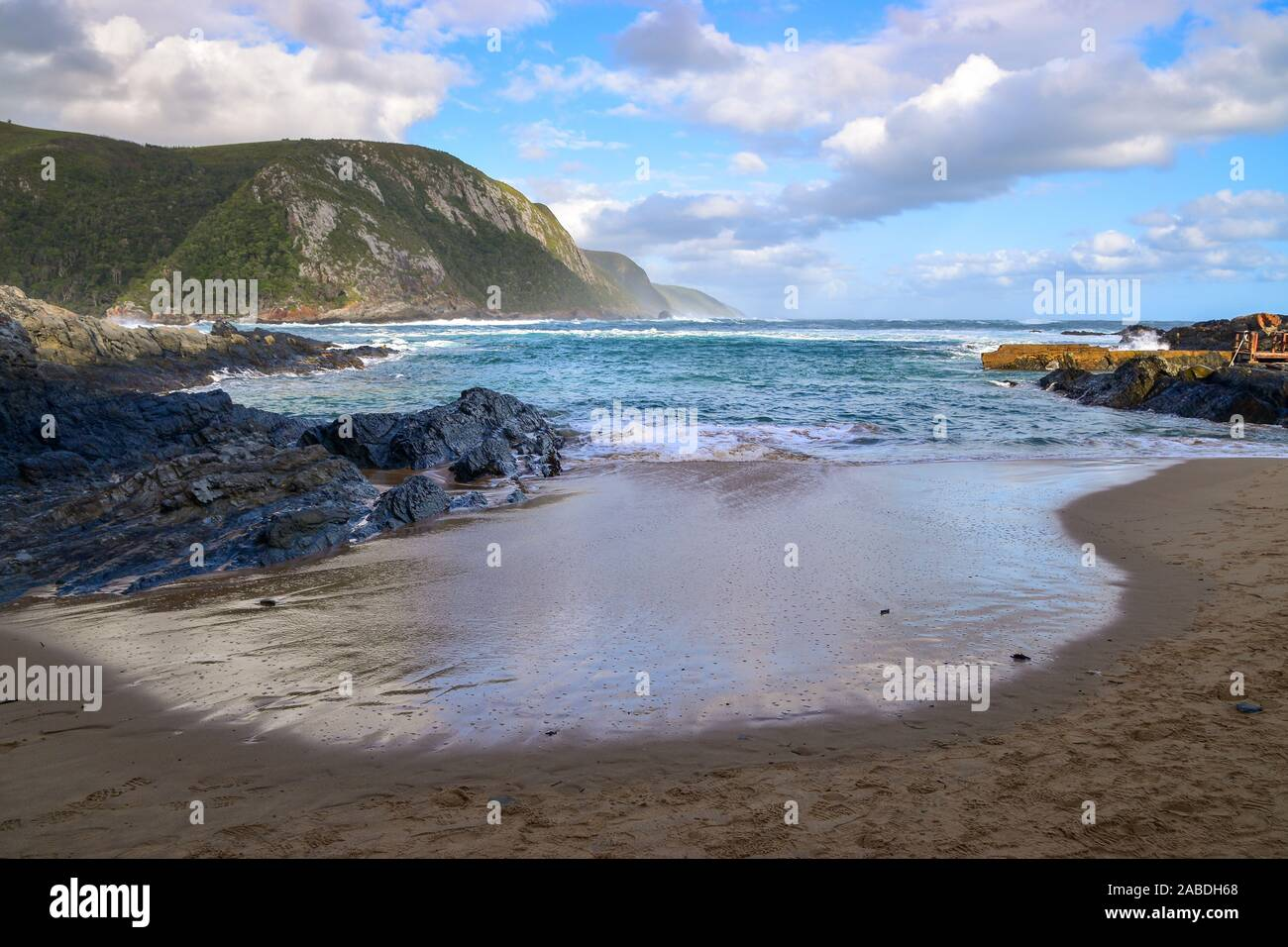 Seascape with sandy beach, blue ocean and green mountains, Tsitsikamma National Park, Garden Route, Eastern Cape, South Africa Stock Photo
