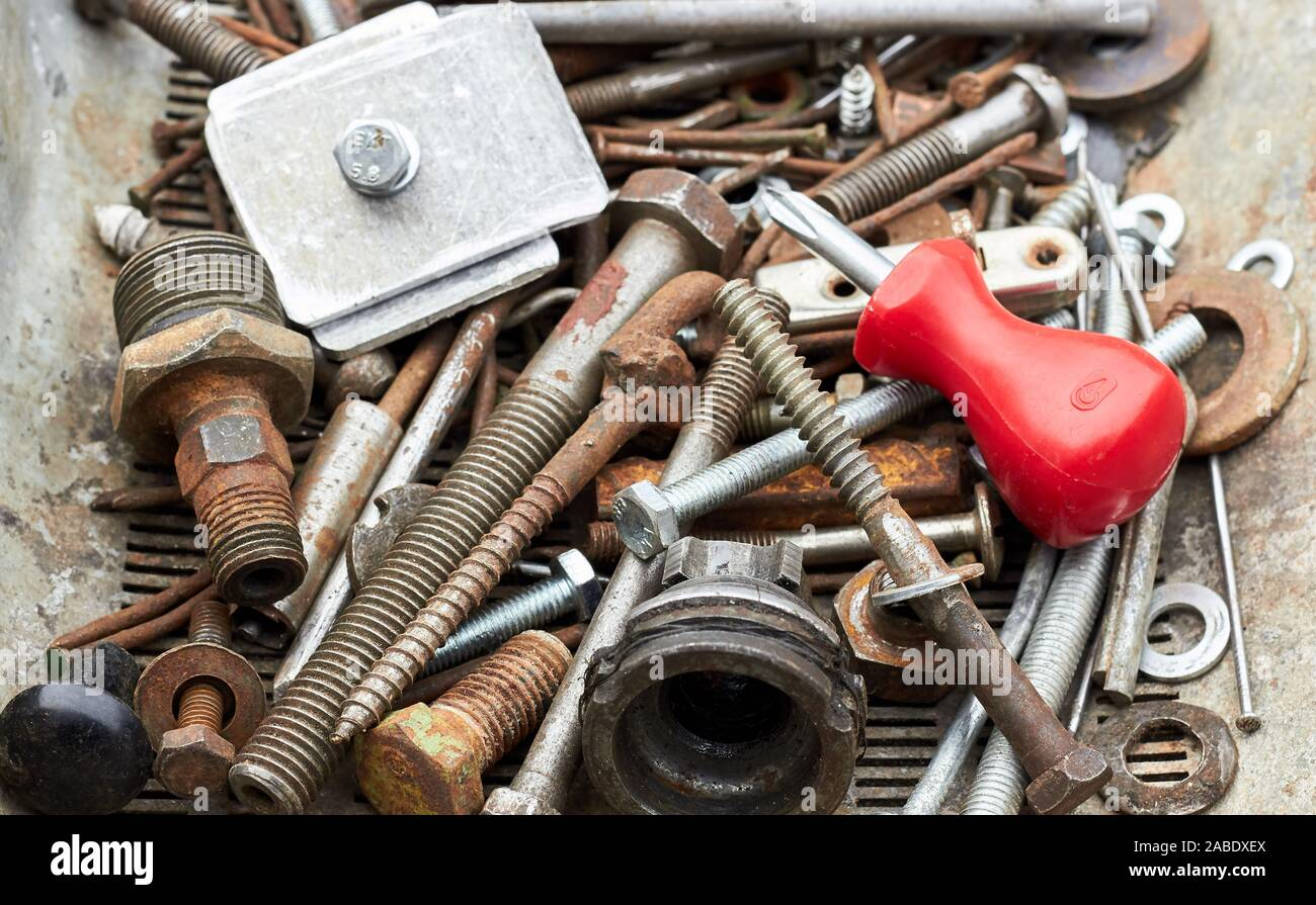 Metallic corroded  industrial waste: rusty bolts and nuts with red  screw driver on the top of the heap, close-up, copy space, recycle hardware backgr Stock Photo