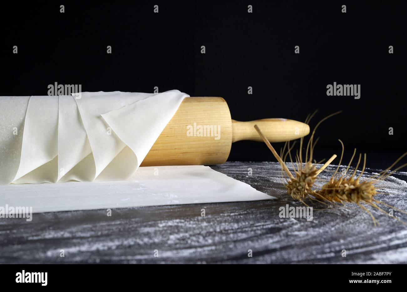 Closeup of phyllo dough on a floured table. Dark background with rolling pin and ears of wheat. Stock Photo