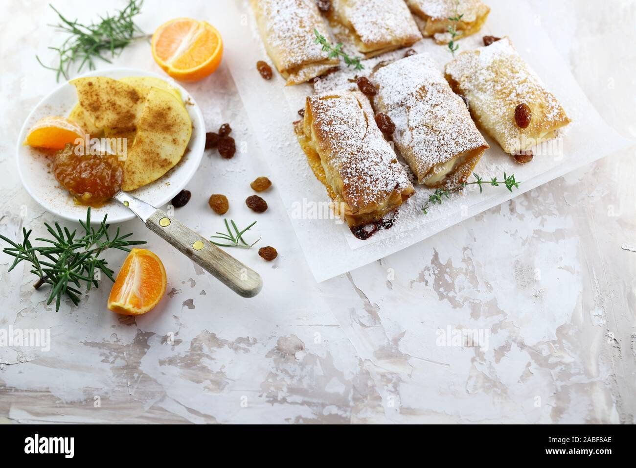 Top view of homemade phyllo dough rolls with apples and orange marmalade. White background with sultanas. Stock Photo