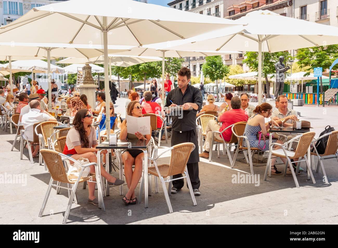 People ordering drinks at bar tables on Plaza de Santa Ana, Barrio de las Letras, Madrid, Spain Stock Photo