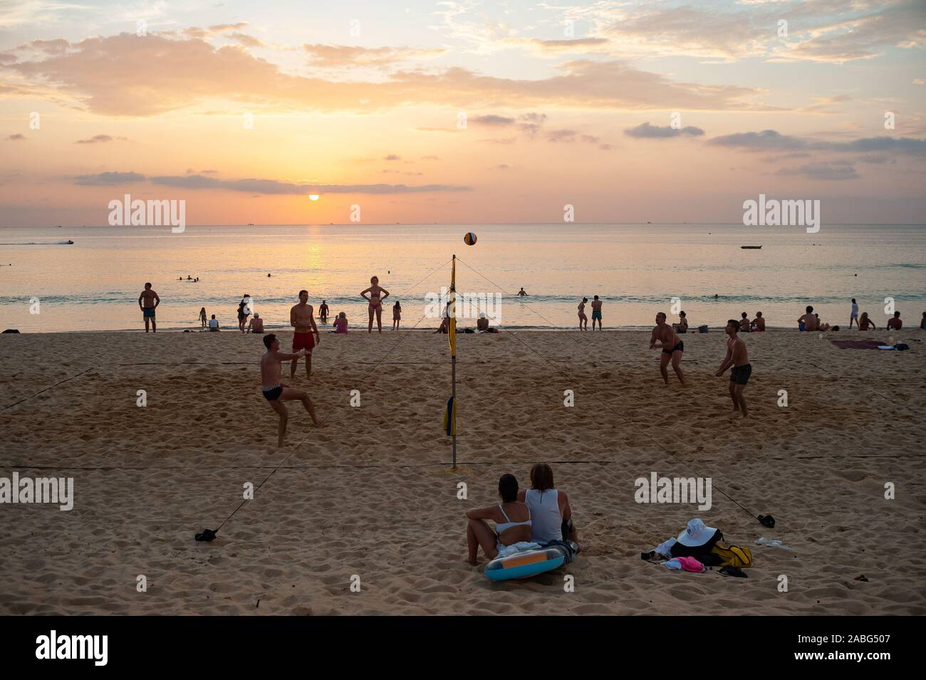 18.11.2019, Phuket, Thailand, Asia - A group of tourists plays volleyball in the sunset on Karon Beach. Stock Photo
