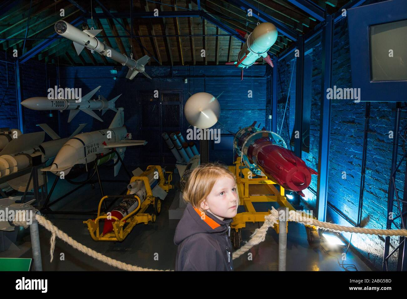 Arrangement display exhibition of vintage missiles and young girl tourist at the Explosion Museum of Naval Firepower; the Royal Navy's former armaments depot of Priddy's Hard, in Gosport. UK (105) Stock Photo