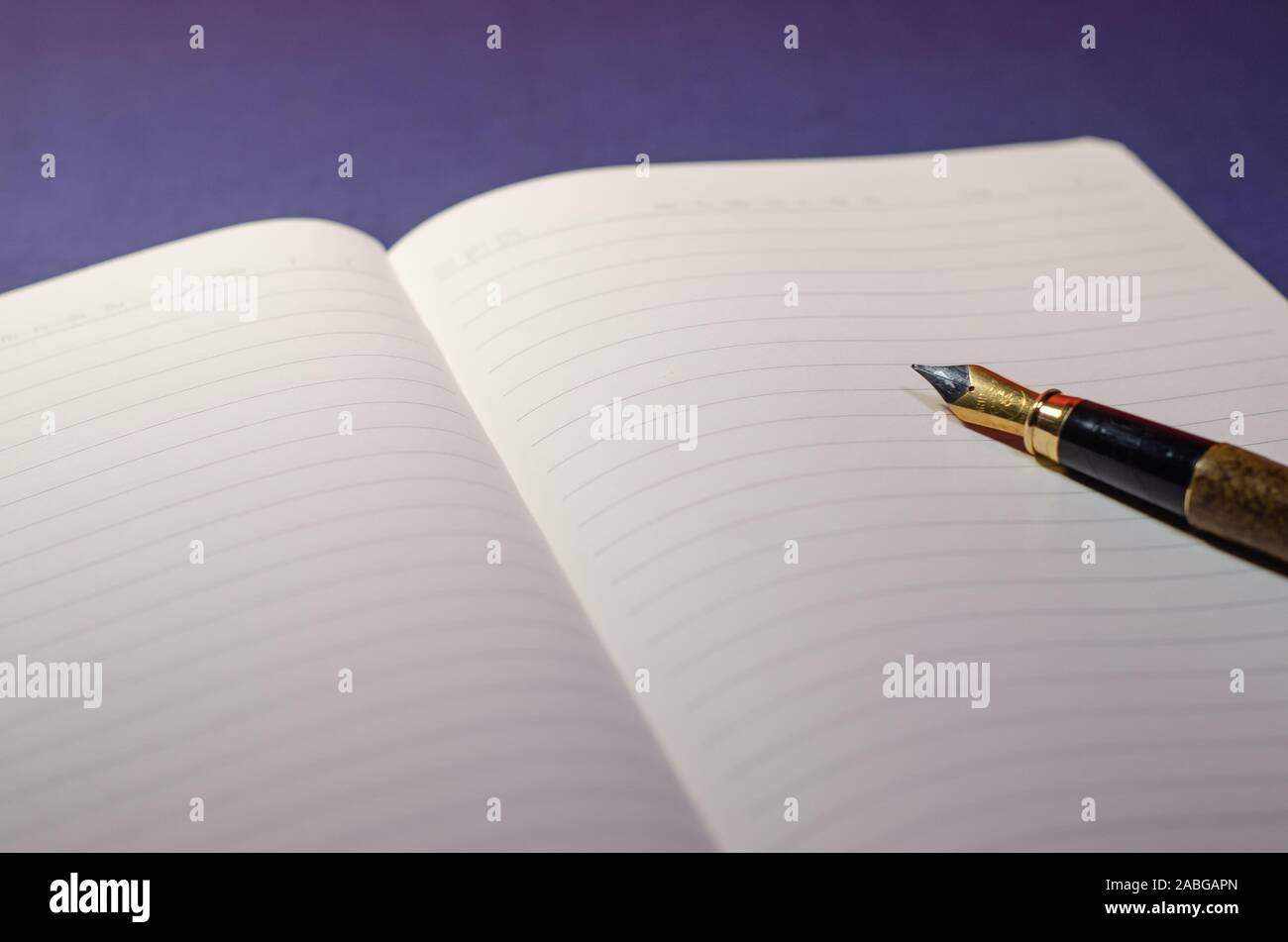 Close view of the tip of a pen writing on an open agenda or notebook with blank pages. Writing on paper with pen ink. Blue surface, wallpaper or deskt Stock Photo