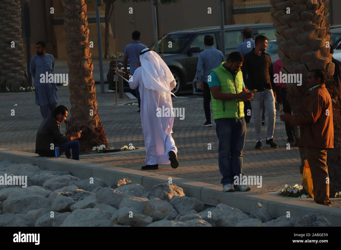 Kuwaiti man in traditional white robe (dishdasha) talking on the phone with Asian expatriates around him on the sidewalk Stock Photo