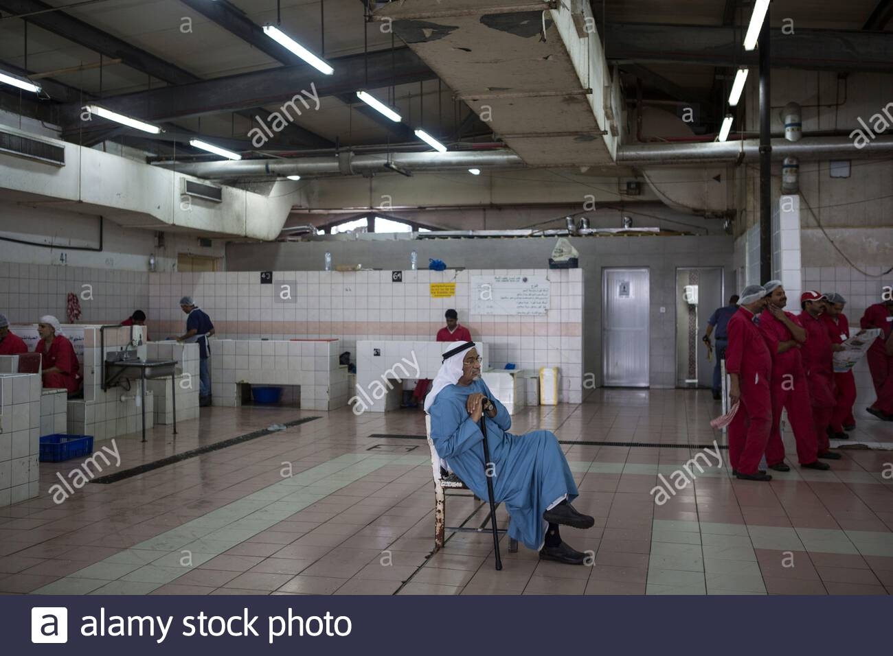 United Arab Emirates - Abu Dhabi - An old Emirati man sitting and waiting for his fish to be cleaned at the Fish market. Stock Photo