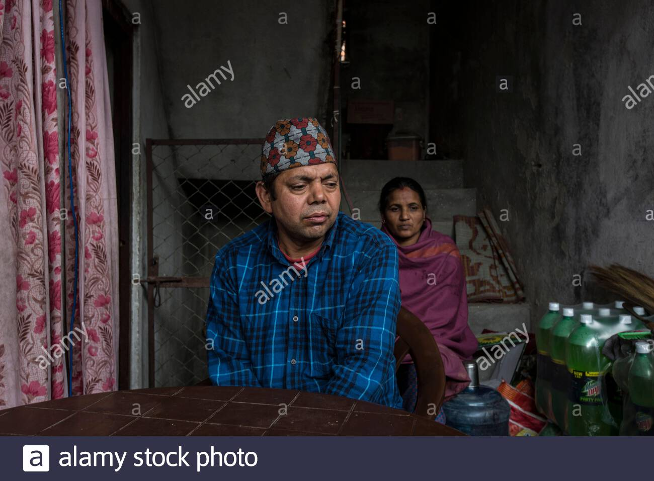 Nepal - Kathmandu - Chom Prasad Panthi (left), 45-year-old, in his house in New Baneshwor, Kathmandu, where he owns a grocery shop along with his wife (right). Originally from the village of Arkhale-5 in the central district of Gulmi, two years ago Panthi Stock Photo