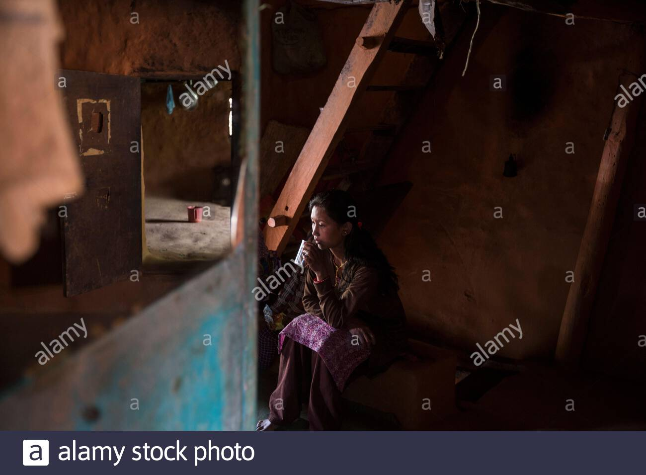 Nepal - Kathmandu - Sunita Lama, 24, drinks a cup of tea while sitting in her house in the outskirts of the capital. Sunita's husband, Sir Kumar Lama, 30, has just come back from Qatar, where he spent one year working as a welder in a factory. Rather than Stock Photo