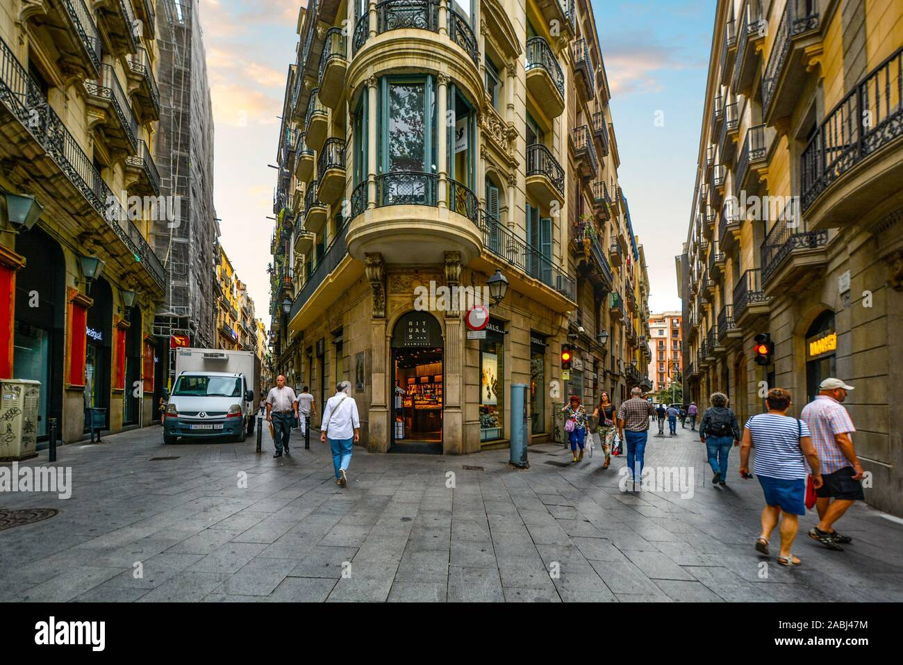 Tourists and locals start their day early as stores open for business at a beautiful intersection of streets in the Gothic Quarter of Barcelona Spain. Stock Photo