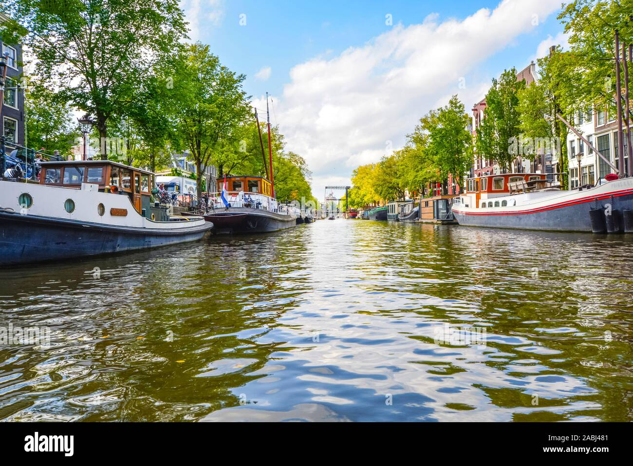Water level view from a tour boat in Autumn of a residential canal filled with boats and houseboats in Amsterdam, Netherlands. Stock Photo