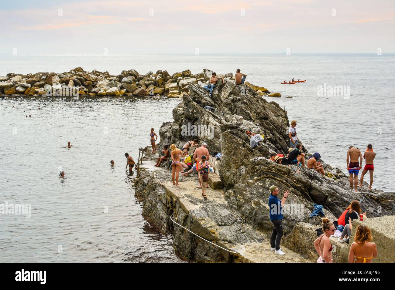 Tourists swim the rocky coastline of the Ligurian Sea off the village of Manarola, in the Cinque Terre region of Italy on an overcast late afternoon Stock Photo