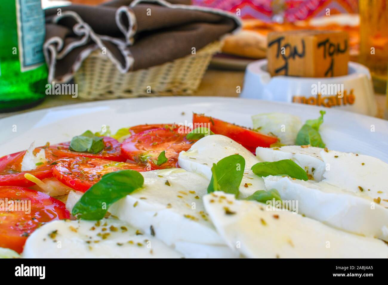 A colorful caprese salad, basket of bread and bottle of water on a table in an outdoor sidewalk cafe in Brindisi Italy. Stock Photo