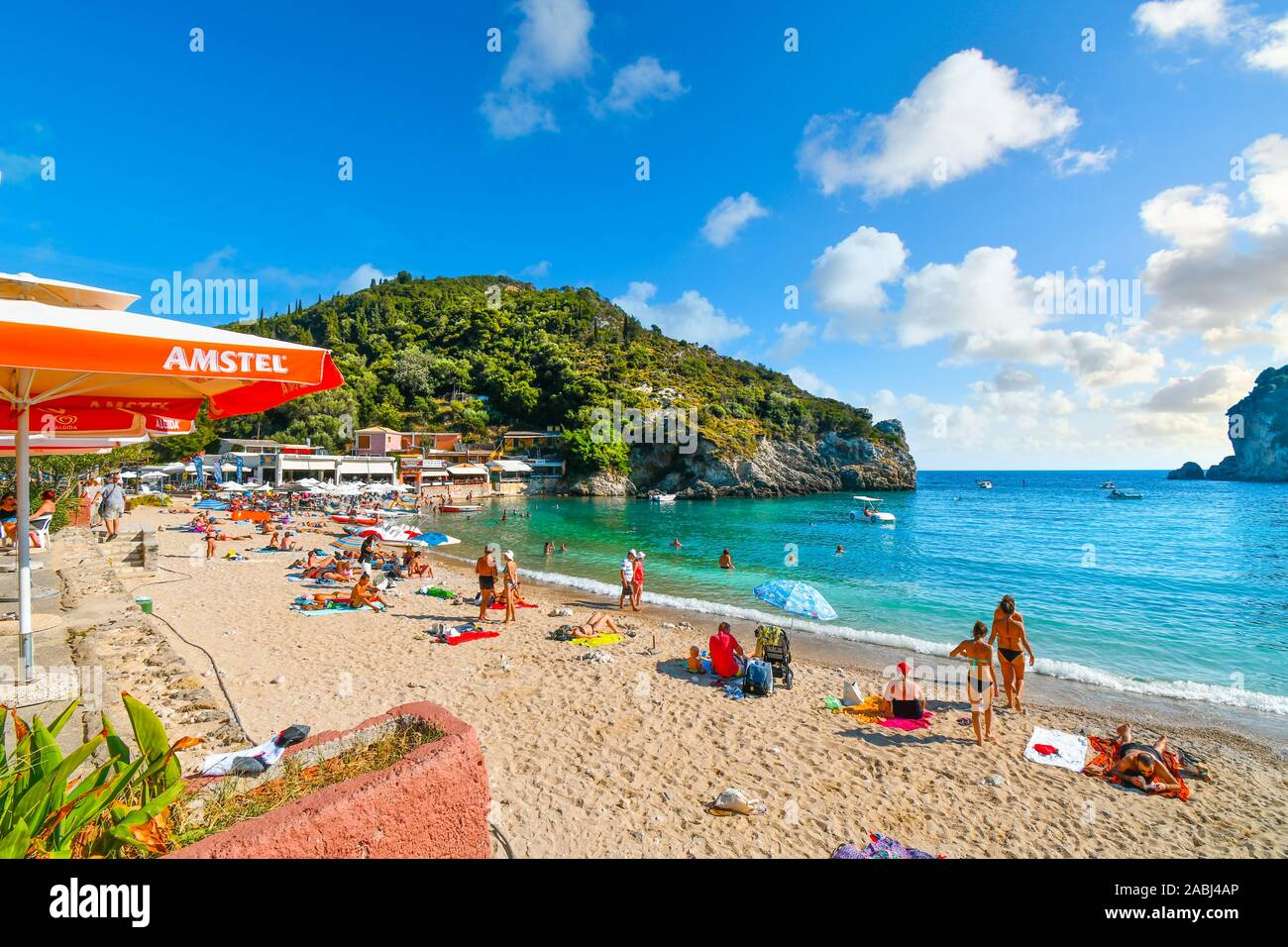 Tourists relax and swim in the clear turquoise waters and on the sandy Palaiokastritsa beach on the Aegean island of Corfu, Greece. Stock Photo