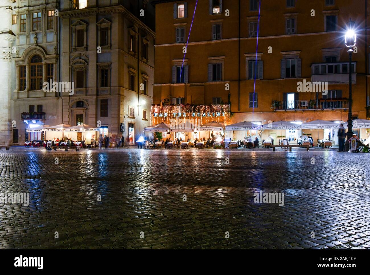 Late night on the Piazza Navona as beams of purple rocket flares lite up and cafes empty and tourists go back to their hotels. Stock Photo
