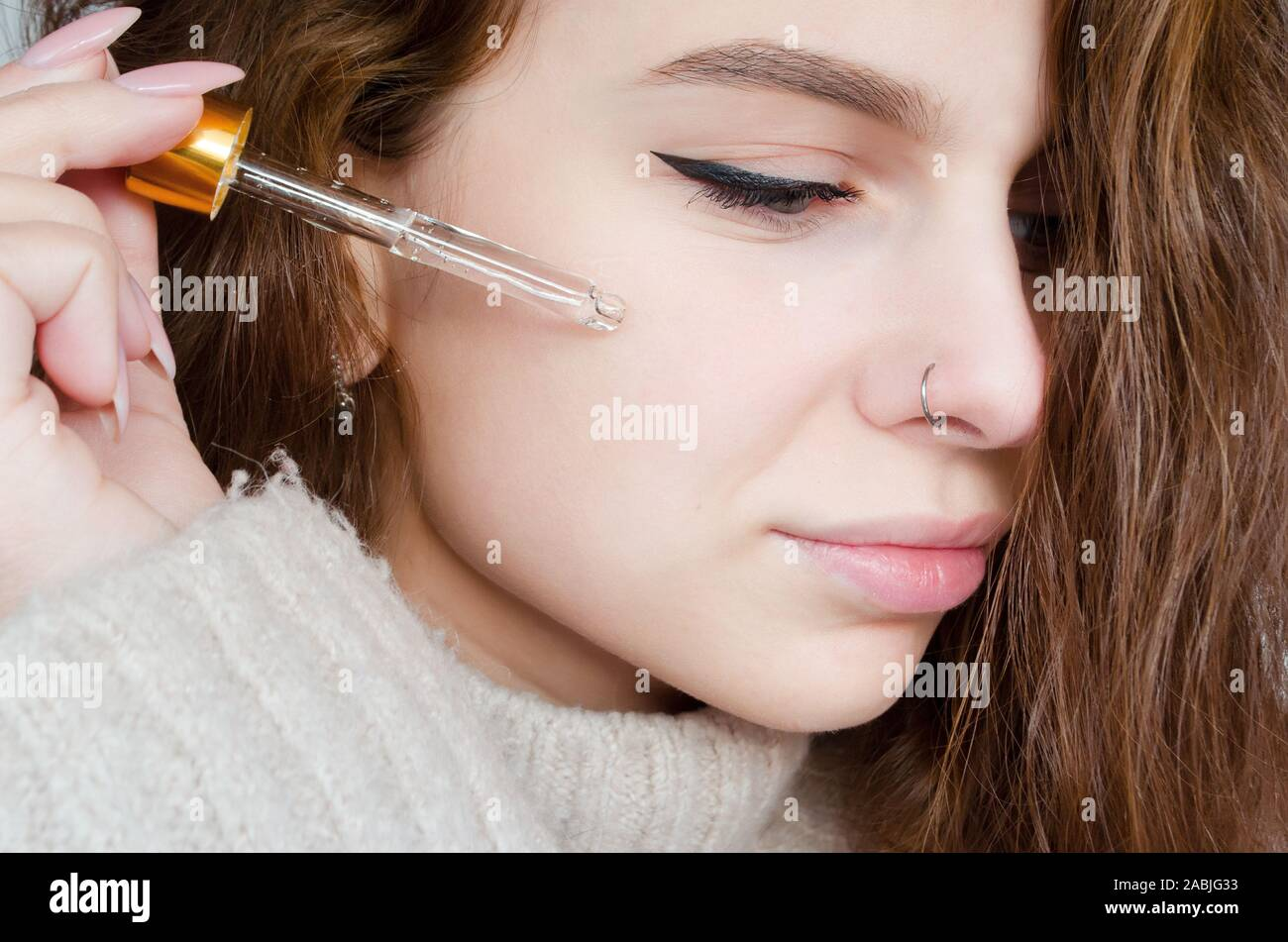 Curly young beautiful woman in warm knitted clothes with pierced nose uses face serum. Winter facial skin care concept. Stock Photo