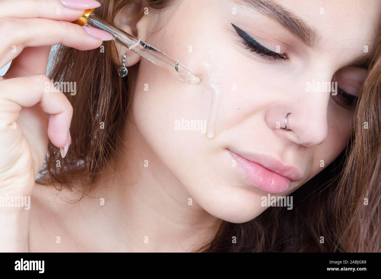 Curly young beautiful woman with piercing nose uses face serum. Face skin care concept. Stock Photo