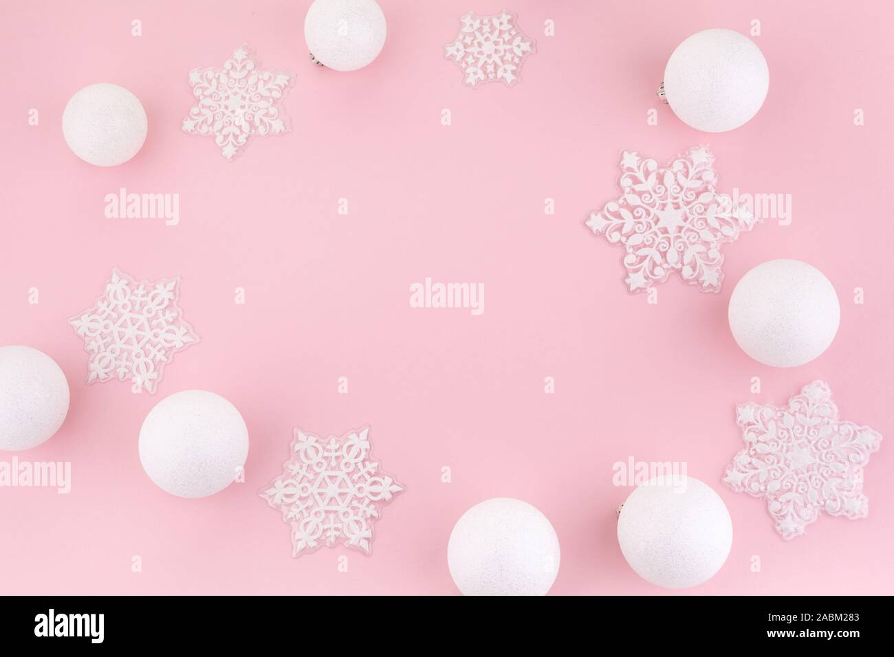 frame made of white christmas decoration with christmas glass balls on pink background christmas wallpaper flat lay 2ABM283