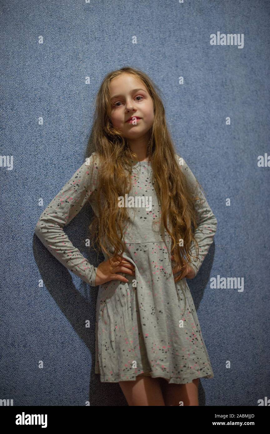 Girl eight years old in a gray knitted dress on a background of blue or blue wall indoors. Cute girl eleven years old with blond long hair in a gray d Stock Photo