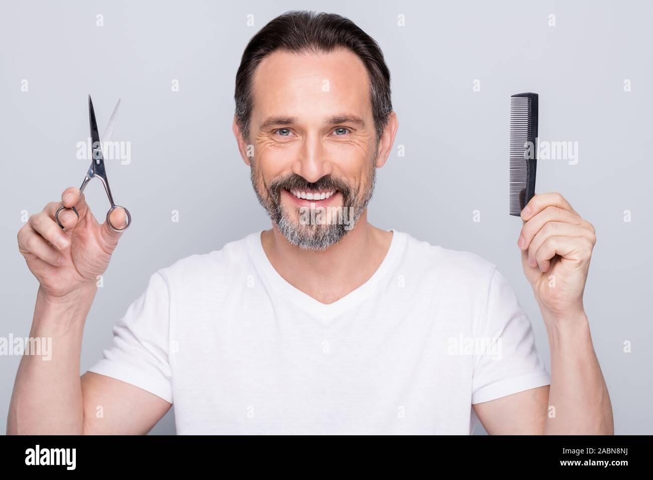 Closeup photo of mature guy metrosexual holding new hairbrush cosmetology hairdo scissors advising option cutting or brushing wear white t-shirt Stock Photo