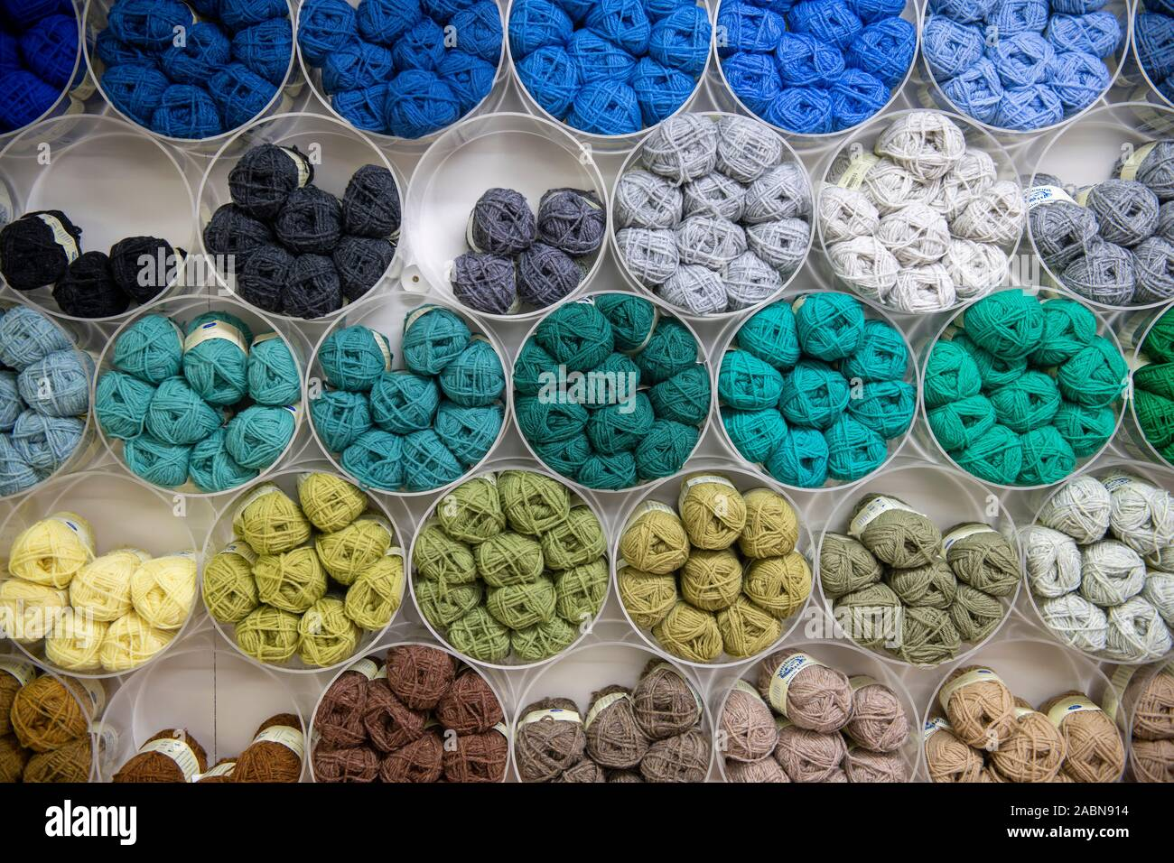 Selection of different coloured wool yarn on display on a wall in Shetland wool shop Stock Photo