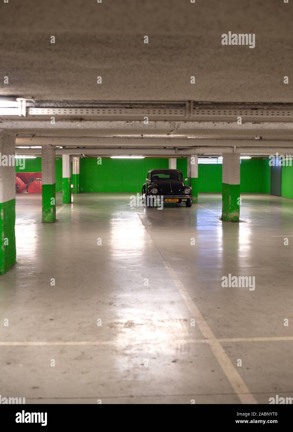 Strasbourg, France - Dec 21, 2016: Vertical image of black cabriolet convertible Volkswagen Beetle mini car parked in empty underground green wall parking Stock Photo