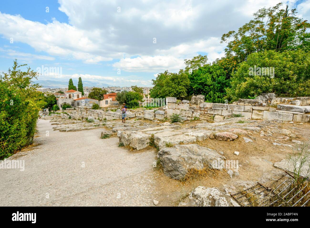 A young couple embraces as they enjoy the view of the city of Athens Greece from the ancient Agora at the base of the Acropolis Hill in the Plaka dist Stock Photo