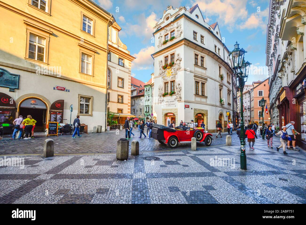 Tourists sightsee, shop and enjoy the cafes as they pass by a vintage red automobile in a picturesque section of Old Town Prague, Czech Republic. Stock Photo