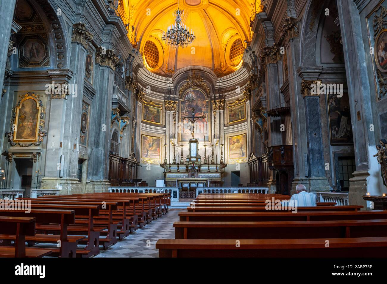 Interior view of the baroque Saint Francois de Paule Church in the Cours Saleya area of Old Town Nice France as an unidentified man prays in the pews Stock Photo