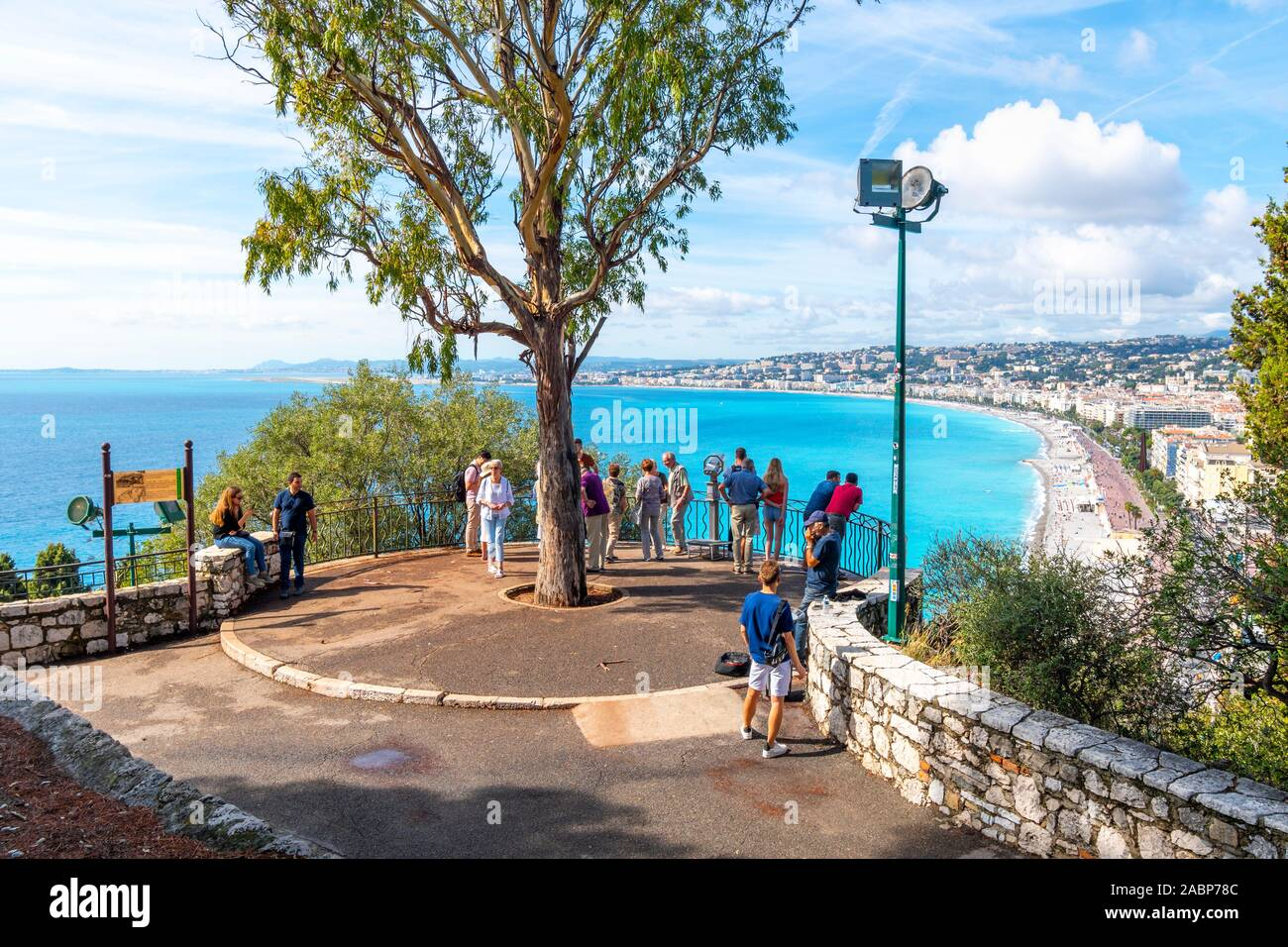 Tourists visit Castle Hill overlooking the turquoise Mediterranean Sea and the city of Nice France, on the Riviera as a busker plays harmonica nearby Stock Photo