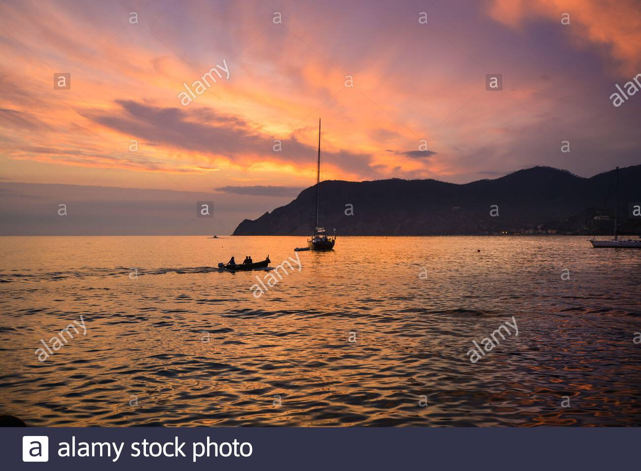 Sunset silhouette view of a small boats in the harbor of Vernazza, Cinque Terre Italy under a colorful pink and purple sunset. Stock Photo