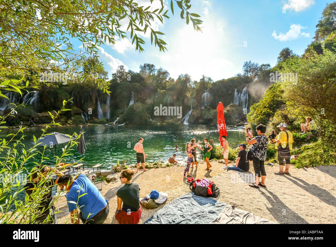 Local Bosnian families enjoy a day at the sandy beach at Kravica Falls near Mostar, Bosnia and Herzegovina. Stock Photo