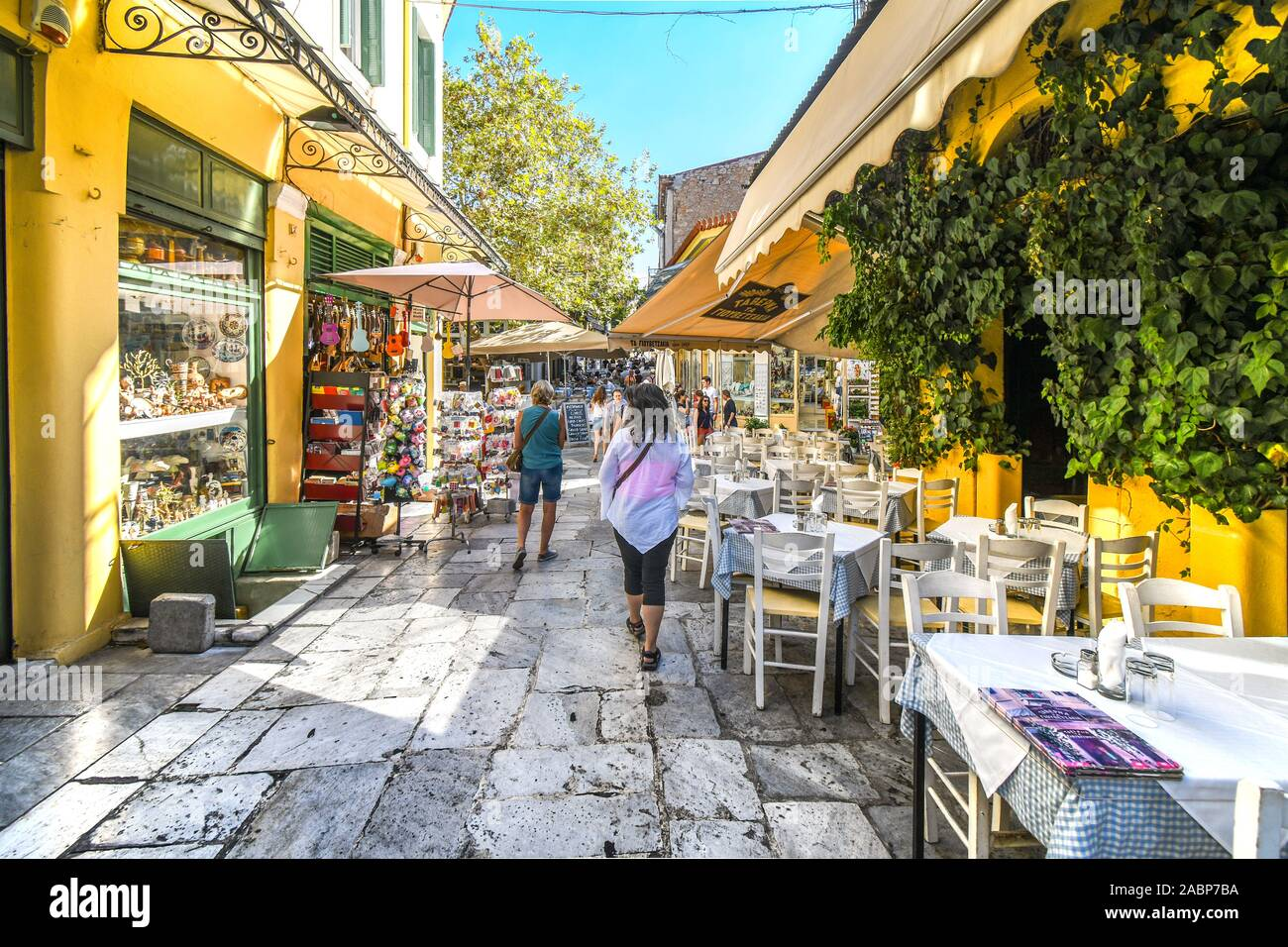 Tourists walk past cafes and shops through narrow streets and alleys in the touristic Plaka district in the heart of historical Athens, Greece Stock Photo
