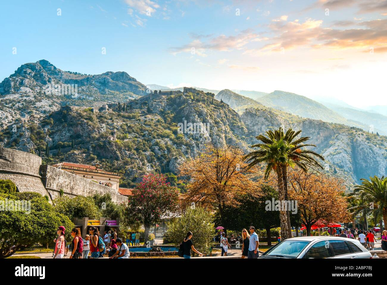 Tourists pass the exterior of the walled city of Kotor as the Castle of San Giovanni and the Montengro mountains rise above late afternoon in summer Stock Photo