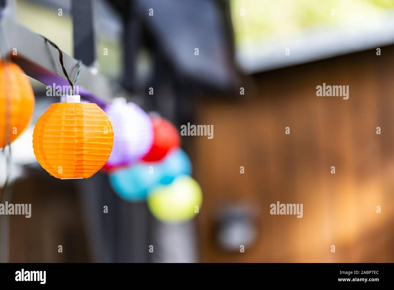 Little colorful lampion lights hanging on a pavilion in a garden on a sunny summer day. Cozy Chairs and Table standing underneath it. Stock Photo