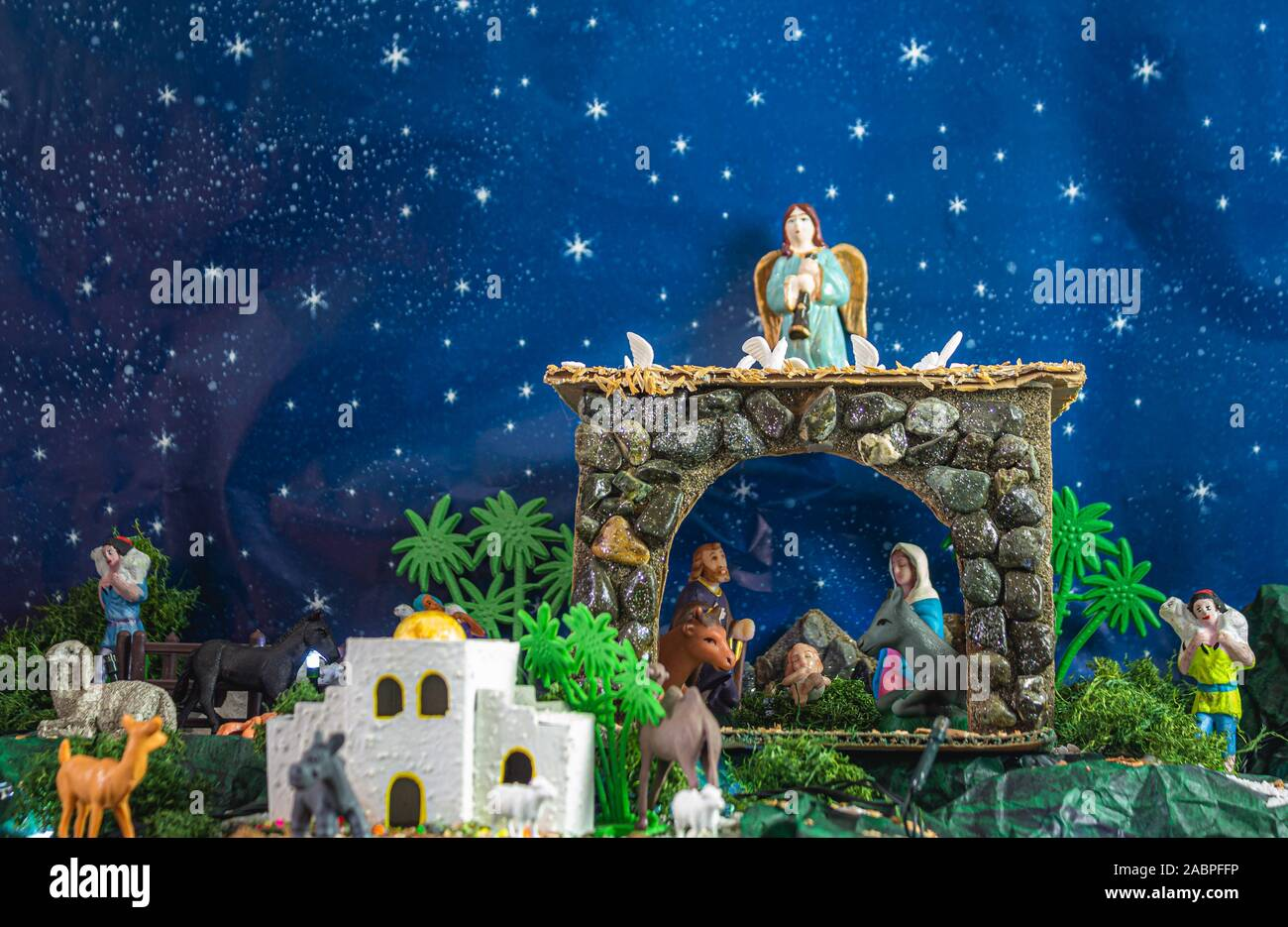 Traditional nativity scene of the birth of the child Jesus in a manger. Virgin Mary, Jose and the baby Jesus are seen with a donkey and a cow. On the Stock Photo
