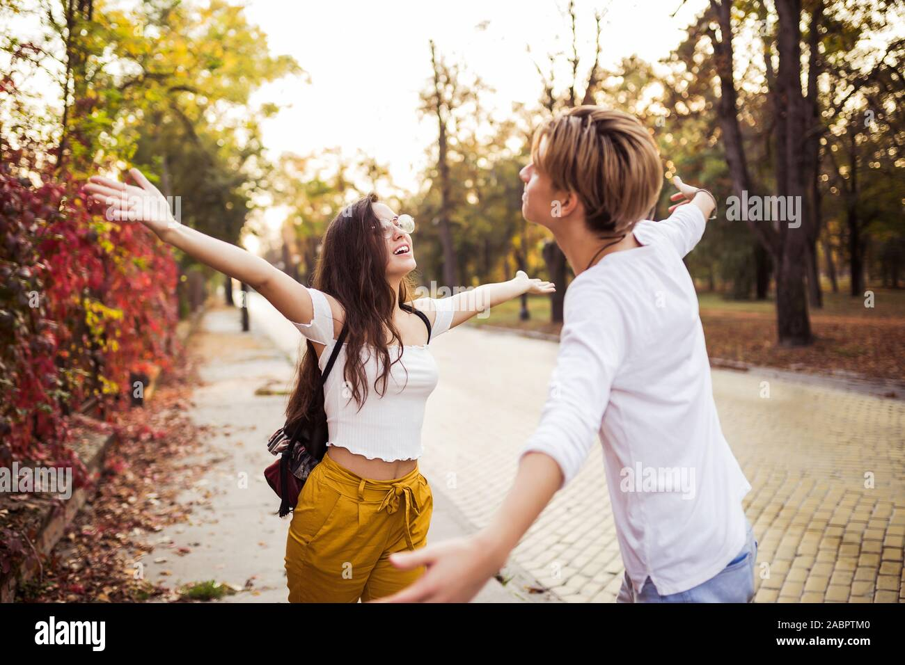 Young man meeting his girlfriend with opened arms on the street Stock Photo