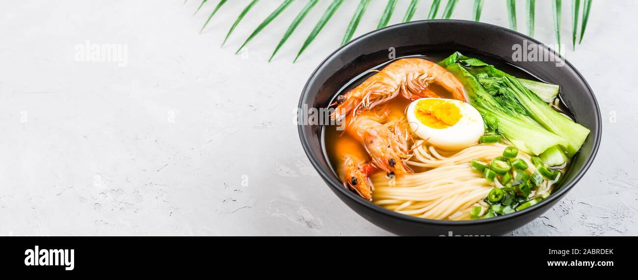 Asian noodle soup, ramen with prawn shrimp, vegetables and egg in black bowl on gray concrete background. Flat lay, Top view, mock up, overhead Stock Photo