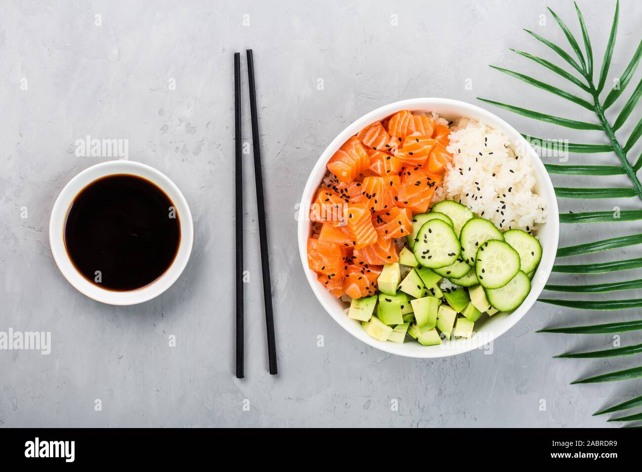 Hawaiian salmon bowl with cucumbers, avocado, sesame seeds and rice. Top view, overhead, flat lay, mock up, template. Healthy food concept Stock Photo