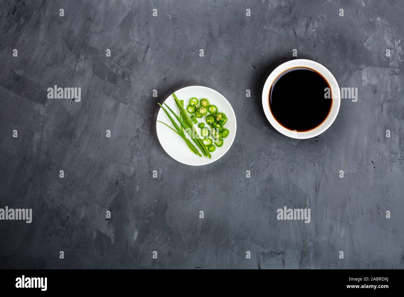 Soy sauce, onion and green pepper on gray concrete background. Flat lay, Top view, mock up, overhead, template Stock Photo