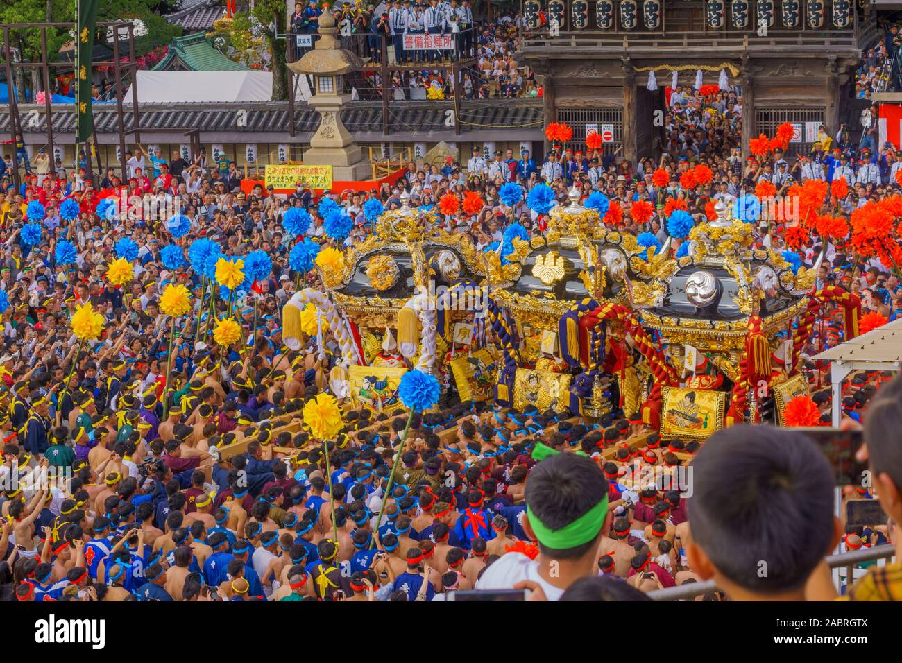 Himeji, Japan - October 14, 2019: Portable shrine carried by men in traditional dressing, and crowd in front of the Matsubara Hachiman Shrine. Part of Stock Photo