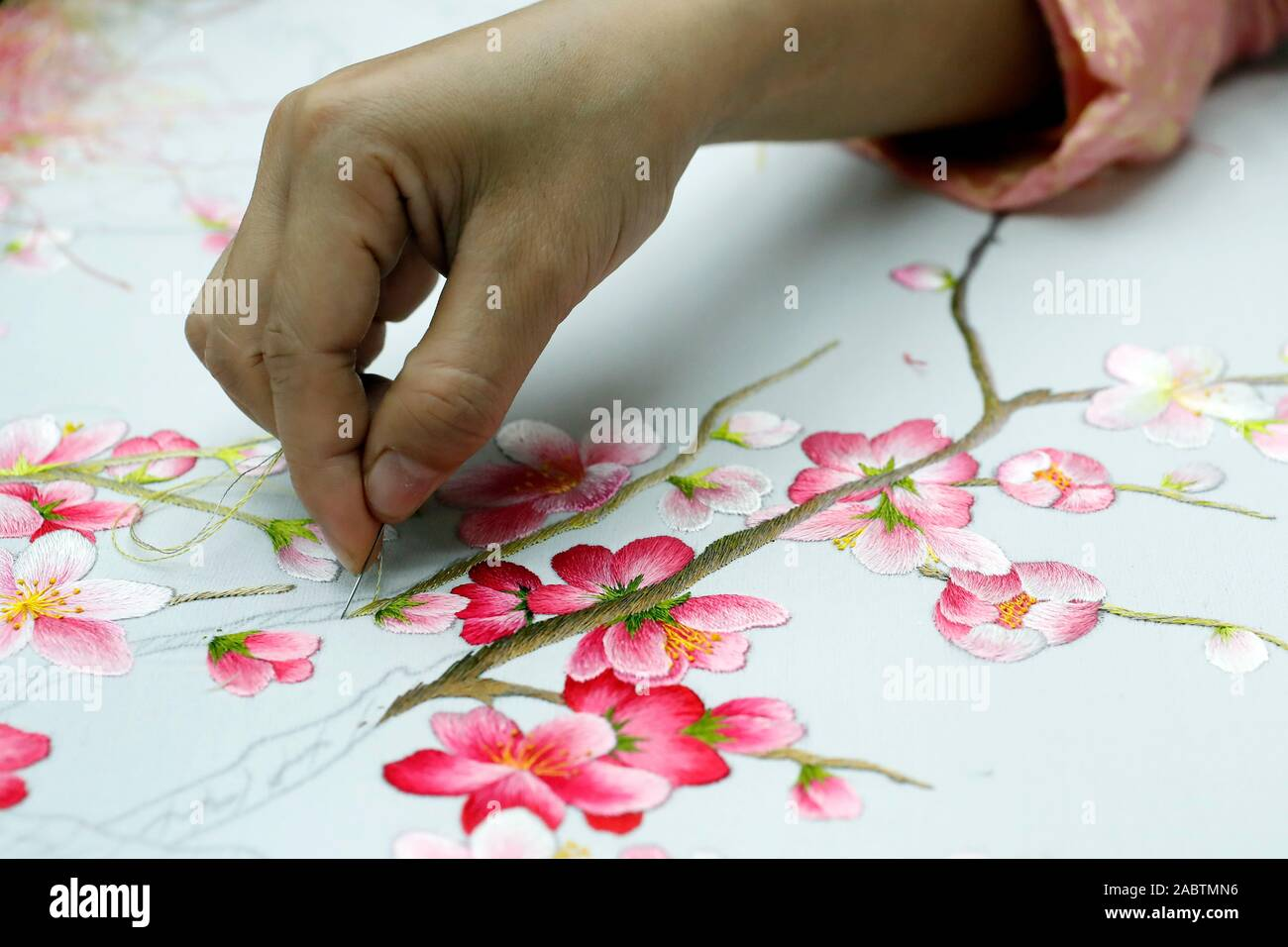 Young female workers doing embroidery. Flowers. Close up on hand ...