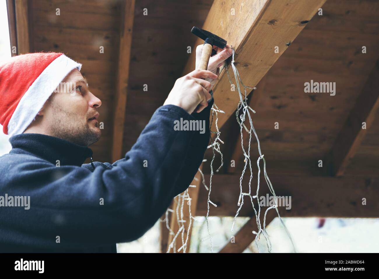 Man With Santa Hat Decorating House Outdoor Carport Installing Christmas Lights Stock Photo Alamy