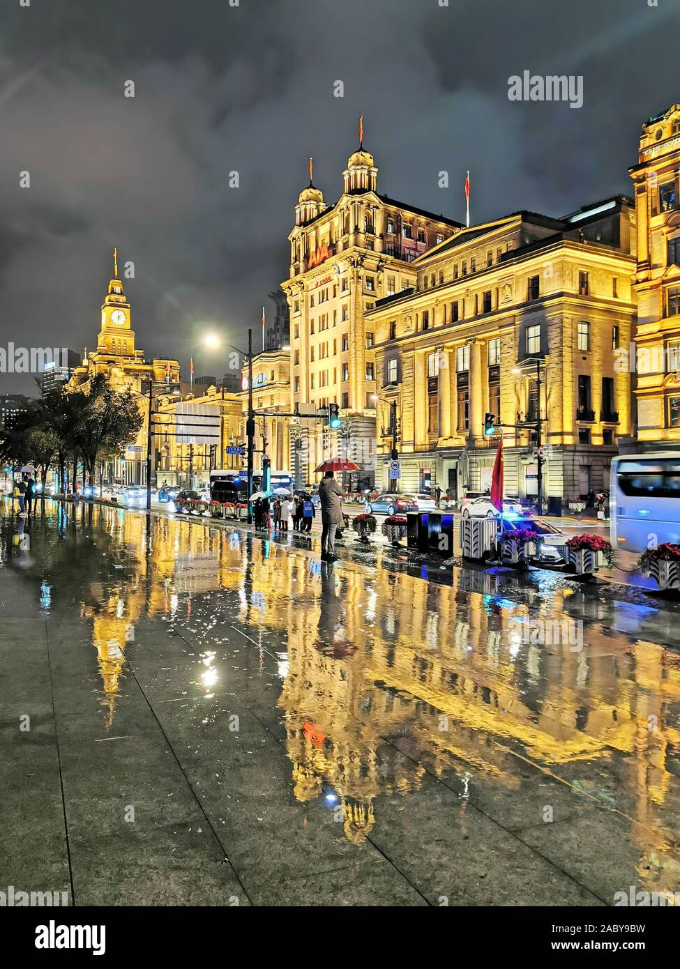 Night view of a reflection of the illuminated century-old western-style buildings on the wet ground in the rain at the promenade along the Bund in Sha Stock Photo