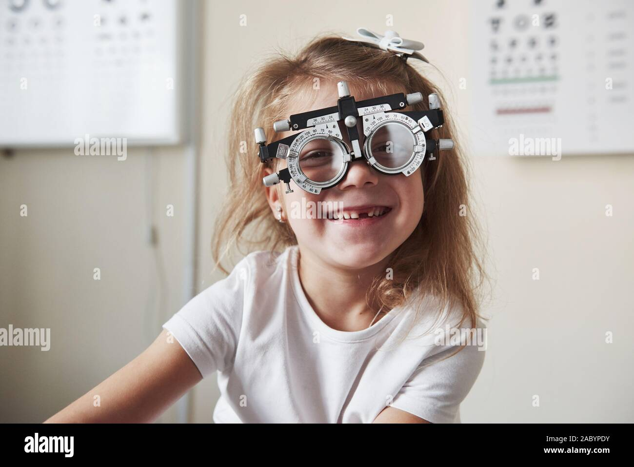 I can finally see everything. Focused portrait of little girl in phoropter looking straight into the camera and smiling Stock Photo