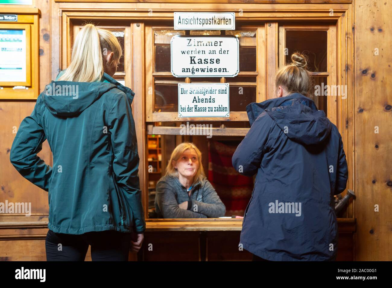 Two female mountain hikers talking to a woman at the reception desk of the Berliner Hütte, Zillertal, Tyrol, Austria Stock Photo